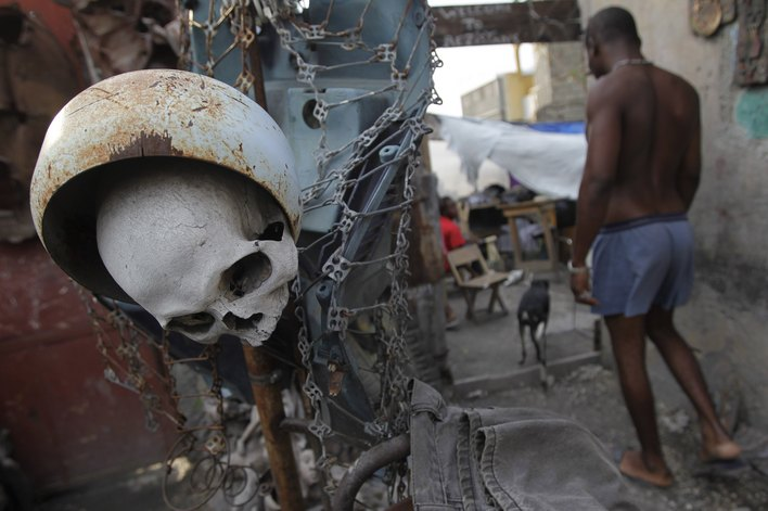 "A Haitian man walks past a sculpture made with a human skull at the ""Atis-Rezistans"" (Artists Resistan) handcrafted museum at Port-au-Prince"