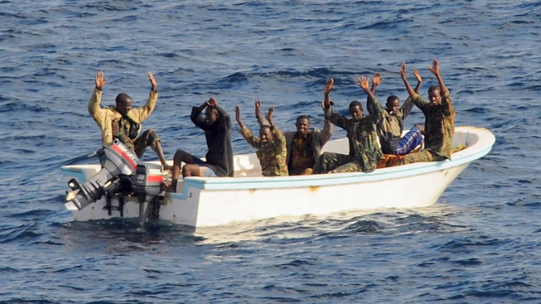 Suspected pirates keep their hands in the air before being arrested in the Gulf of Aden