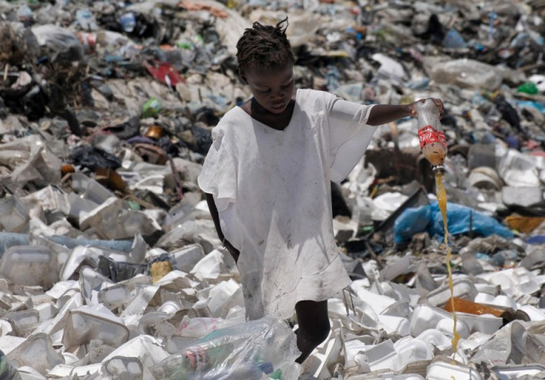 A-child-wades-through-a-sea-of-styrofoam-and-plastic-containers-looking-for-plastic-bottles-that-the-family-will-sell-for-money-in-the-slum-area-of-Citi-Soliel-in-Port-au-Prince-on-September-13-2011.-ReutersSwoan-Parker-960x670