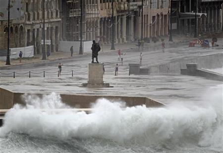 Waves crash against Havana's seafront boulevard 'El Malecon' as tourists take pictures
