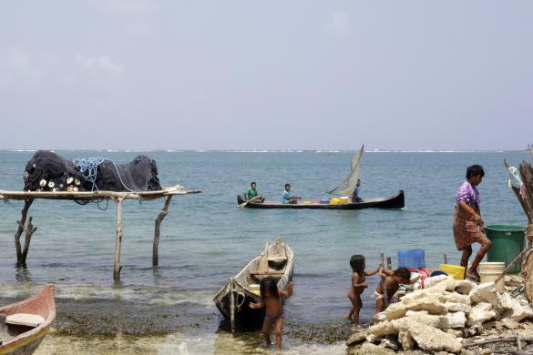 Children play at the beach as a local boat passes by the coast of Caledonia island in the region of Guna Yala