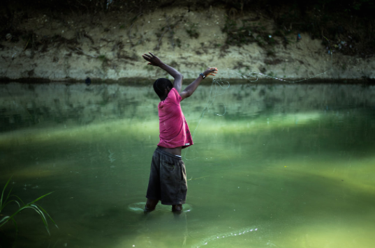 A young Haitian fishing in the Latem River, known to be contaminated. The country is still struggling to stem a cholera epidemic. Ian Willms for The New York Times