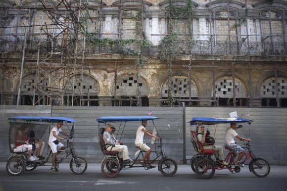 Tourists ride in pedicabs in Havana