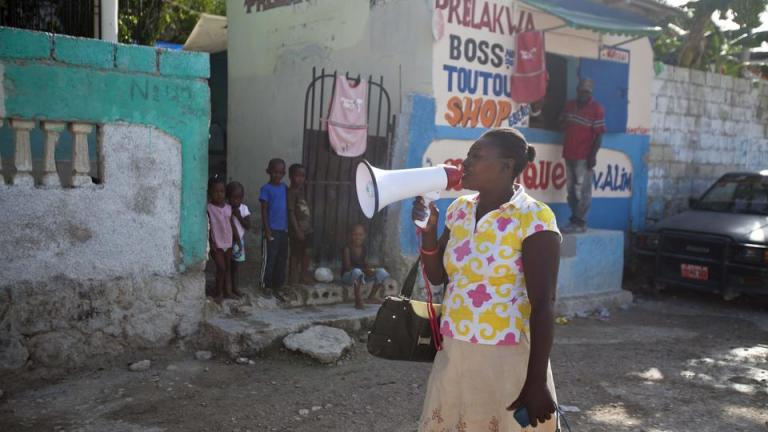 "In this May 8, 2015 photo, volunteer Anne-Marie Saintou announces that only special needs children will be treated, or allowed to live at the Mercy & Sharing residential center, as she walks in the seaside community of Luly in Arcahaie, Haiti. Saintou is part of a campaign by the nonprofit organization to warn people about promoters and recruiters for orphanages who roam the countryside offering money, or false promises, to desperate parents struggling to raise children, and she speaks from bitter experience. ""Ladies, say 'NO!' she shouts. ""We will not give away our children anymore."" (AP Photo/Dieu Nalio Chery)"