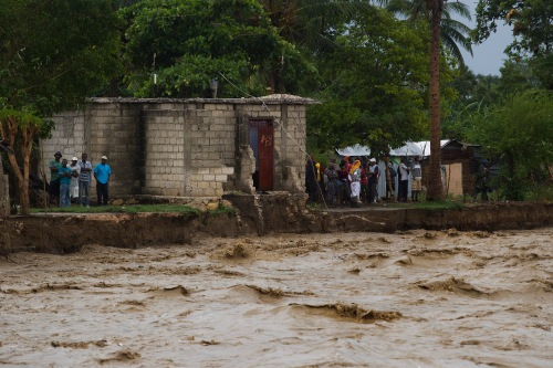 Residents stand on the banks of a river that swept away five homes in Port au Prince. Hurricane Sandy passed to the west of Haiti October 25, 2012 causing heay rains and winds, flooding homes and overflowing rivers. Photo Logan Abassi UN/MINUSTAH