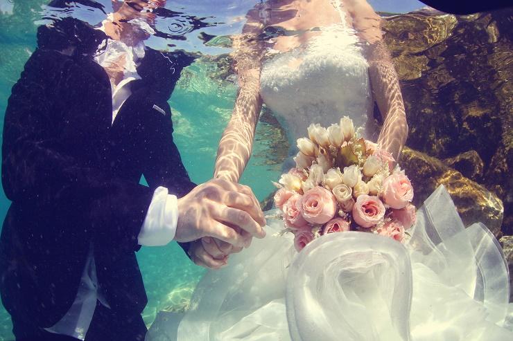 Capture of Bride and groom holding hands underwater