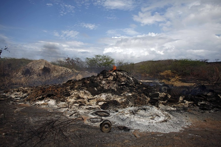 Fire burns a pile of military vehicle parts and disabled and non-live artillery and mortar shells on what was once the former U.S. Naval training range on Vieques Island off Puerto Rico, Saturday, May 4, 2013. For decades, warships and planes hammered the facility before it was closed in 2003, leaving behind thousands of unexploded bombs, rockets, and other munitions which are now being painstakingly cleared. The clean up is expected to take another decade. (AP Photo)