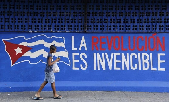 "A boy walks past a graffiti reading ""The revolution is invincible"" in Havana"