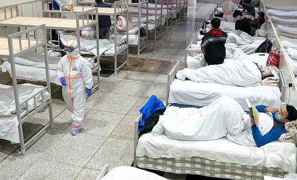 Medical workers in protective suits attend to patients at the Wuhan International Conference and Exhibition Center